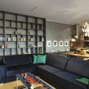 Bogactwo półek w salonie umożliwia zebranie pokaźnej domowej biblioteki. Duży narożnik w granatowym kolorze i seledynowe poduszki, nadają surowemu wnętrzu przytulnego charakteru, ale nie zaburzają wizualnego ładu. Projekt: Biuro Architektoniczne GAO Arhitekti. Fot. Miran Kambic.