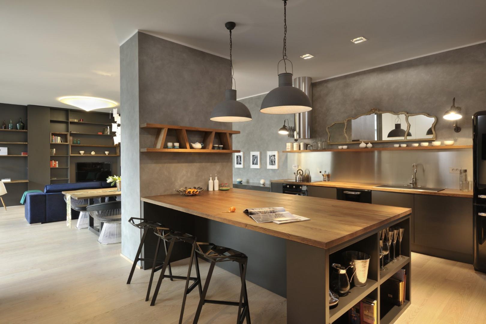 Salon od kuchni oddziela niewielka ścianka działowa, poprowadzona przez centrum otwartej przestrzeni. Zlokalizowano na niej półwysep, który może pełnić funkcję jadalni lub domowego baru. Projekt: Biuro Architektoniczne GAO Arhitekti. Fot. Miran Kambic.