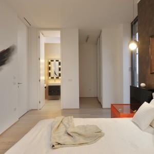 Jedna z sypialni, skomunikowana z łazienką. W tle efektowne lustro w stylu garderoby dawnych gwiazd. Tworzy we wnętrzu unikalny klimat, razem z miedzianą ramą lustra nad łóżkiem i kolorystycznie komponującą się z nią, ścianą. Projekt: Biuro Architektoniczne GAO Arhitekti. Fot. Miran Kambic.