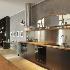 Styl panujący we wnętrzu to fuzja wielu różnych stylistyk. Szara ściana tworzy industrialny klimat, matowe, gładkie fronty szafek to pochwała nowoczesności, natomiast stylizowane lustro i lampy wprowadzają element stylu glamour. Projekt: Biuro Architektoniczne GAO Arhitekti. Fot. Miran Kambic.