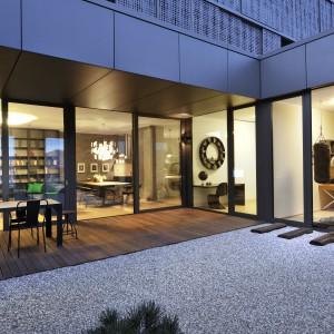 Piękne, eleganckie atrium urządzono w stylu japońskich ogrodów. Na drewnianym deptaku ustawiono duży stół z krzesłami. Otoczenie i komfortowy mebel zachęcają do relaksu na świeżym powietrzu. Projekt: Biuro Architektoniczne GAO Arhitekti. Fot. Miran Kambic.