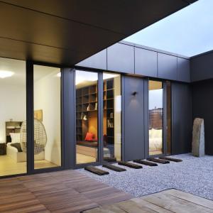 Większość pomieszczeń w mieszkaniu ma bezpośredni dostęp do atrium, z którym połączone są panoramicznymi, dużymi oknami. Oryginalnym elementem aranżacji atrium są stare, drewniane tory kolejowe, które tutaj pełnią rolę kładki, ułożonej na ozdobnych kamieniach. Projekt: Biuro Architektoniczne GAO Arhitekti. Fot. Miran Kambic.