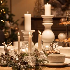 Elegancki stół w bieli, przystrojony klasycznym świątecznym stroikiem. Wśród gałązek ostrokrzewu ustawiono cienkie świeczki i subtelną, srebrną figurkę dostojnego renifera. Pięknie komponuje się on z aranżacją całego stołu, będąc stylowym dodatkiem. Fot. AD Home Loving.