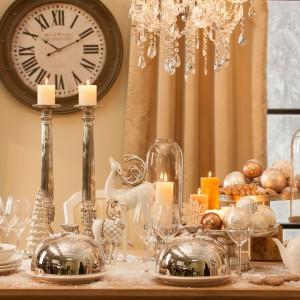 """Piękny świąteczny stół, oprószony sztucznym śniegiem, udekorowany srebrnymi naczyniami. W samym centrum dumnie stoi piękna, biała figurka dumnego renifera. Obok - mniejsza kozica, w złotym """"kubraczku"""". Aranżacji nie brak zarówno filuternego uroku, jak i eleganckiego szyku. Fot. AD Home Loving."""
