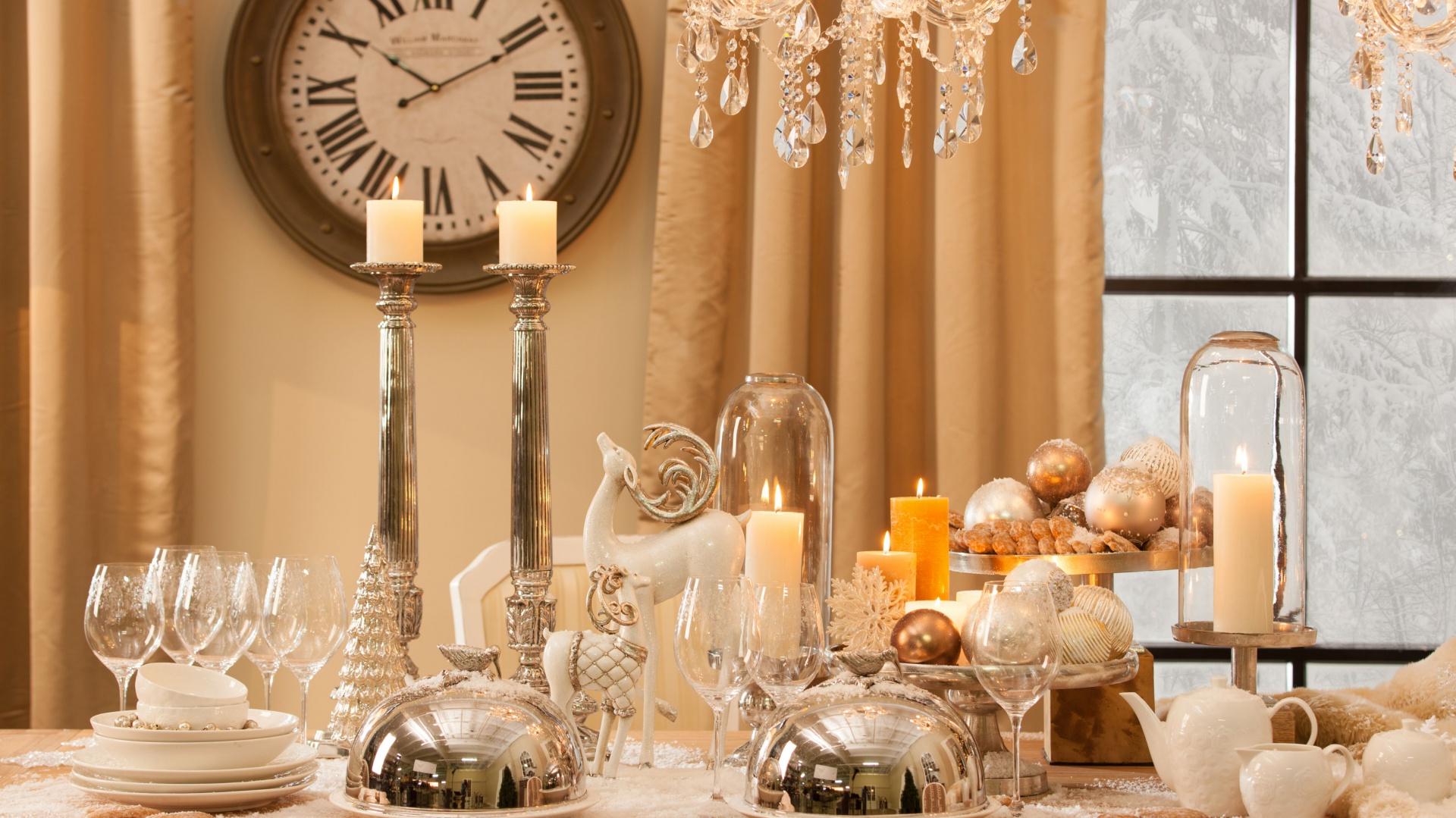 Piękny świąteczny stół, oprószony sztucznym śniegiem, udekorowany srebrnymi naczyniami. W samym centrum dumnie stoi piękna, biała figurka dumnego renifera. Obok - mniejsza kozica, w złotym