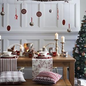 Obrus zastąpiono dwoma mniejszymi obrusami bieżnikami. Na tkaninach ustawiono zastawę stołową, podczas gdy drewniana powierzchnia stołu posłużyła z podstawę dla licznych dekoracji: masywnych świeczników, blaszanych lampionów, czerwonych latarenek oraz - oczywiście - stada reniferów, ubranych w czerwone wstążeczki. Fot. Sainsbury's.