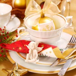 Serwetki na świątecznym stole możemy spiąć serwetnikiem-obrączką, udekorowanym figurką małego cherubinka. Fot. Shutterstock.