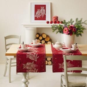 Odświętny charakter stołu podkreśli bukiet ze świerkowych gałązek i czerwonych kwiatów. Fot. Design3000.de.