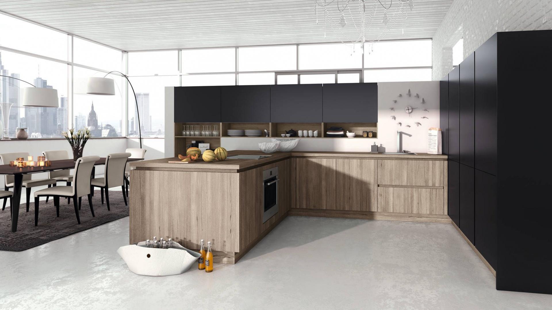 Piękne, eleganckie wnętrze, w którym czarna, zabudowa efektownie kontrastuje z kuchnią w kształcie litery L, utrzymaną w odcieniach kawy z mlekiem. Gładkie fronty bez uchwytów z matowym wykończeniem nadają kuchni stylowy szyk. Fot. Alno, program Alnostar Smartline.