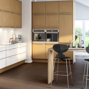 Wysoką zabudową pokryto ściankę działową, odgraniczającą kuchnię od sąsiadującego z nią pokoju. Kolorystycznie zabudowa komponuje się z górnymi szafkami na przylegającej ścianie. Fronty dolnych szafek są białe, ale już cokół komponuje się z zabudową. Fot. Marbodal, kuchnia Torö.