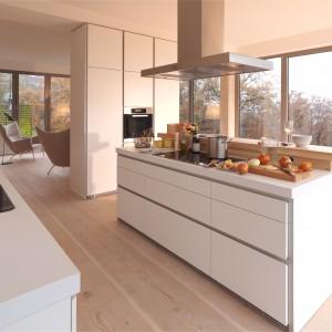 Poprowadzona pod sam sufit, wysoka zabudowa pełni jednocześnie rolę elementu odgraniczającego kuchnię od salonu. Stylistycznie i kolorystycznie meble kuchenne pozostawiono jednakowe: z gładkimi frontami i prostymi, nowoczesnymi liniami. Fot. Bulthaup, linia b1.