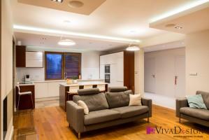 Zdjęcie salonu (parter). Podłoga z litego drewna dębowego olejowanego, w oknach żaluzje drewniane, na ścianie telewizyjnej okładzina ścienna fornirowana. Meble telewizyjne lakierowane. Projekt: Pracownia Projektowania Wnętrz Viva Design, Fot. Tadeusz Poźniak.