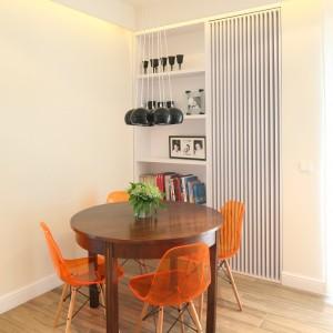 Okrągły stół, kolorowe krzesła, a nad nimi eleganckie oświetlenie - to pomysł na niewielką jadalnię w rogu salonu. Projekt: Dominik Respondek. Fot. Bartosz Jarosz.