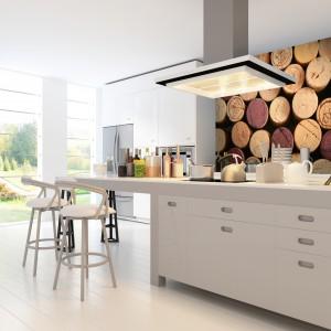 Fototapeta z motywem korka w różnych odcieniach brązu pięknie wprowadza ciepły kolor do białej, chłodnej aranżacji kuchni. Fot. Dekornik.
