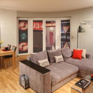 W urządzonej w stylu soft-loft strefie dziennej prym wiedzie duża kanapa narożna. Tuż za nią ustawiono klasyczny drewniany stół na cztery osoby, który wyznacza przestrzeń jadalni. Projekt: Iza Szewc. Fot. Bartosz Jarosz.