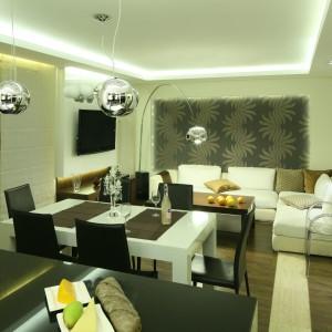 W eleganckiej strefie dziennej kuchnia płynnie łączy się z salonem, a obie przestrzeni stylistycznie spaja stół, który stanął na granicy obu przestrzeni. Projekt: Agnieszka Hajdas-Obajtek. Fot. Bartosz Jarosz.