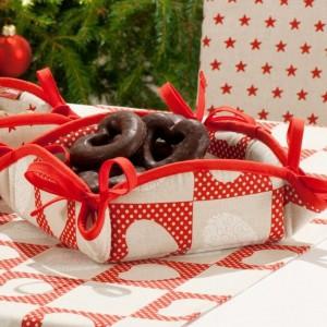 Kwadratowy koszyk na pieczywo, z kokardkami, wykończony lamówką, której kolor może być dobrany w zależności od tkaniny. Kolekcja tkanin Christmas. 31,90 zł, Dekoria. Fot. Dekoria.