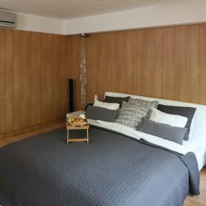 Okładziny ścienne oraz szafy zostały wykonane z drewnopodobnego dekoru w wybarwieniu wiśnia malaga. Dzięki zastosowaniu jednakowego materiału na fronty zabudowy oraz ściany, szafy stają się prawie niewidoczne, zlewają się z wykończeniem ścian. Dodatkowo podłoga laminowana o podobnej barwie potęguje naturalny, a zarazem nowoczesny wystój sypialni. Projekt: Małgorzata Błaszczak. Fot. Bartosz Jarosz.