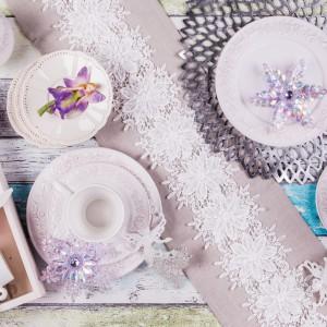 Biała, zdobiona porcelana w zestawieniu z białymi, dekoracyjnymi kwiatuszkami, przywodzącymi na myśl płatki śniegu. Fot. Home&You.
