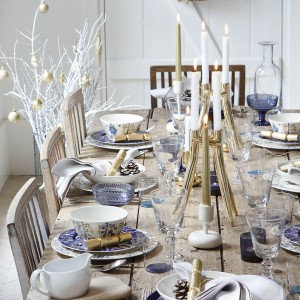 Stół z surowego drewna przystrojono białą zastawą z niebieską dekoracją. Całości dopełniają proste kieliszki i białe drzewko przy stole. Fot. Amara.