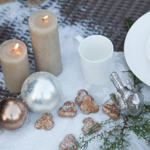 Przyprószony śniegiem stół urokliwie komponuje się z białymi talerzykami, bombką i srebrna figurką ptaka. Aranżację delikatnie ocieplają beżowe świeczki i dwie złote bombki. Fot. AD Loving Home.