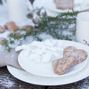 Stół przykryto białym obrusem i oprószono śniegiem. Talerzyk ozdobiono delikatną tekstylną dekoracją w białym kolorze. Fot. AD Home Loving.