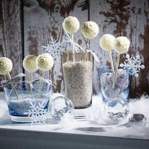 Niezwykle oryginalny pomysł na zimową aranżację stołu. W szklankach o różnej wysokości i szerokości umieszczono białe, dekoracyjne kamyczki, w które wetknięto przysmaki z białej czekolady. Patyczki owinięto białymi wstążeczkami, a wokół szklanek ułożono przezroczyste szklane bombki i ozdobne, białe śnieżynki. Pomysłowo i z klasą! Fot. Villeroy&Boch.