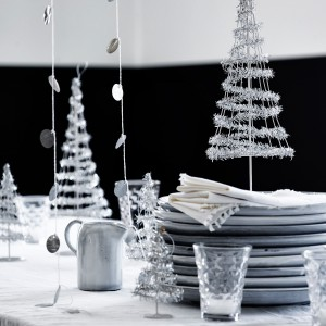 Stół pokryto białym, tiulowym obrusem, na którym stanęły posrebrzane dekoracje w postaci metalowych, urokliwych choinek. Fot. Tine K Home.