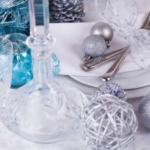 Zachwycająca aranżacja stołu. Błękit w postaci szklanej latarenki i ażurowych bombek zestawiono z pięknymi kryształami, posrebrzanymi ozdobami choinkowymi i białym obrusem. Srebrne sztućce udekorowano przezroczystą wstążką ze srebrną lamówką i dekorem w kształcie gwiazdek. Fot. Shutterstock.