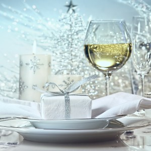 Wokół zastawy stołowej rozsypano na stole posrebrzane śnieżynki. Biel porcelany komponuje się estetycznie z białą serwetką oraz pudełeczkiem, zapakowanym w biały papier i srebrną wstążkę. W tle gruba, biała świeca z motywem srebrnej śnieżynki. Fot. Shutterstock.