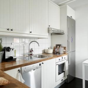 Piękna kuchnia w stylu skandynawskim. Dominującą we wnętrzu biel ociepla drewniany blat. Lekko frezowane fronty szafek w połączeniu z klasycznymi płytkami na ścianie nad powierzchnią roboczą, nadają kuchni domowy charakter. Fot. Stadshem.