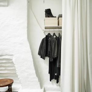W niewielkiej wnęce ściennej, za białą zasłoną, zlokalizowano wieszaki na ubrania i praktyczną półkę na buty. Oryginalna, stara ściana pełni funkcję oryginalnej dekoracji. Fot. Stadshem.