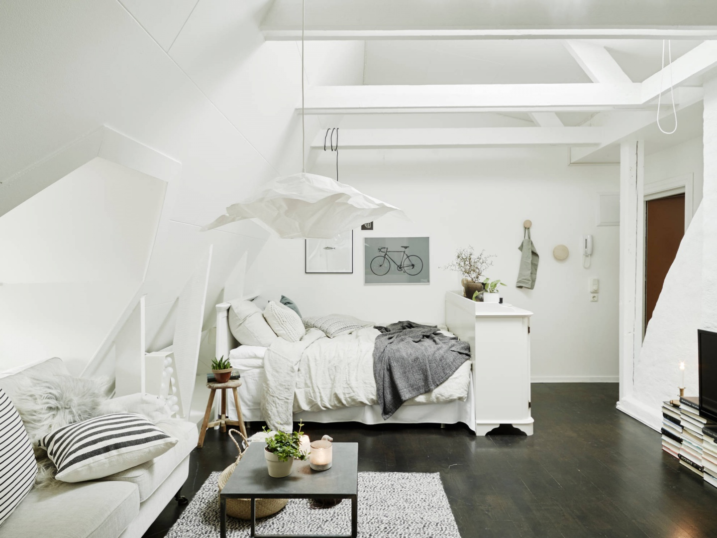 W otwartej przestrzeni mieszkania urządzono kuchnię, salon oraz sąsiadującą z nim sypialnię. W nogach łóżkach ustawiono niewielką komodę, która osłania przestrzeń do spania od bezpośredniego kontaktu z holem wejściowym. Fot. Stadshem.