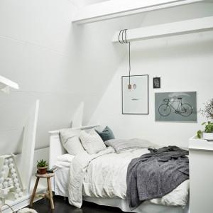W rogu otwartej przestrzeni urządzono przytulną sypialnię, odgrodzoną od holu wejściowego jasną, stylizowaną komodą. Belki stropowe nad łóżkiem posłużyły za miejsce zawieszenia oświetlenia, zastępującego nocną lampkę. Fot. Stadshem.