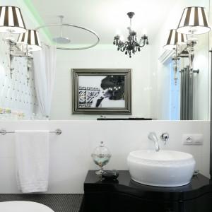 W tej łazience postawiono na mocno dekoracyjne oświetleni. Kinkiety umieszczone po obu stronach lustra są niezwykle stylowe i eleganckie. Doskonale pasują do kolorystki i stylu wnętrza. Projekt: Małgorzata Galewska. Fot. Bartosz Jarosz.