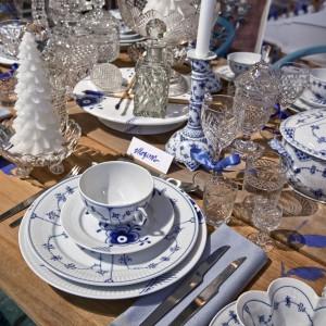 Bogato udekorowany stół pozwolił na rezygnację z obrusu - jedynymi tekstyliami są ozdobne wstążki i serwetki. Aranżację utrzymano w kolorach bieli i błękitów, z kryształowymi akcentami. Zimowy chłód podkreśla biała świeczka w kształcie choinki, pokrytej śniegiem. Fot. Royal Copenhagen.