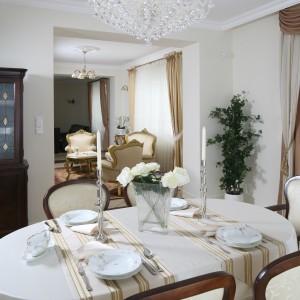 Biały obrus to klasyka eleganckiego nakrycia stołu. Tutaj dodatkowo skomponowano go z bieżnikami w złote pasy. Projekt wnętrza: Małgorzata Goś. Fot. Bartosz Jarosz.