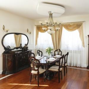 Piękne, stylizowane meble w jadalni utrzymanej w klasycznym stylu sprawiły, że talerze na tekstylnych podkładkach i eleganckie szkło na stole jadalnianym wystarczą jako odświętne nakrycie stołu. Projekt wnętrza: Magdalena Mirek-Roszkowska. Fot. Bartosz Jarosz.
