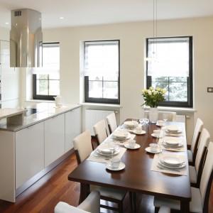 W jadalni sąsiadującej z nowoczesną kuchnią, dekorację stołu również utrzymano we współczesnym, oszczędnym stylu. Elegancka, biała zastawa komponuje się z jasnymi, tekstylnymi podkładkami. Projekt wnętrza: Kinga Śliwa. Fot. Bartosz Jarosz.