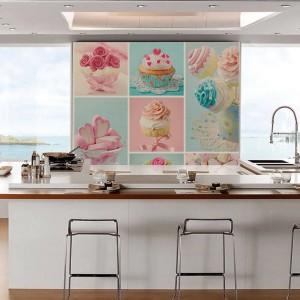 Kolorowa naklejka na ścianę z motywem apetycznych słodkości. Ożywia ona delikatnie białą kuchnię, ocieploną brązowym blatem. Kolaż z kolorowymi babeczkami utrzymany w pastelowych odcieniach jest delikatnym akcentem. Fot. Pixers.