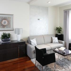 Jasna kolorystyka przestrzeni sprzyja zarówno pracy, jak i wypoczynkowi. Naprzeciwko biurka ustawiono jasnoszarą sofę, do której dobrano ciemne fotele. Projekt: Kinga Śliwa. Fot. Bartosz Jarosz.