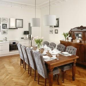 Niezwykle piękna aranżacja przestrzeni kuchni, połączonej z jadalnią. Klasyczne, stylizowane meble w jadalni zestawiono ze współczesnymi meblami kuchennymi. Kompozycję bieli i ciepłego brązu uzupełniono szarymi tapicerkami krzeseł. Projekt: Joanna Kurkowska. Fot. Bartosz Jarosz.