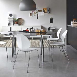 W kuchni, w której dominują szarości jaśniejszymi elementami są nowoczesne, białe krzesła. Lekko industrialną aranżację ocieplają beżowe motywy w postaci dywanu i... drewnianych akcesoriów kuchennych. Fot. Kler, model krzesła Basil.