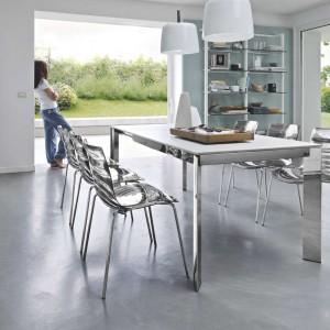 Do nowoczesnych mebli kuchennych jak znalazł pasuje nowoczesny jadalniany stół i dopasowane krzesła. Szary blat i połyskujące, metalowe nogi od stołu wprowadzają do wnętrza element futurystycznego klimatu. Fot. Kler, stół Baron.