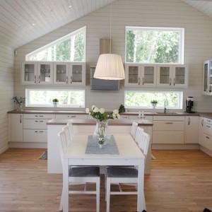 Przytulna kuchnia z jadalnią. Białe meble doskonale pasują kolorystycznie do białego stołu jadalnianego. Spójną kompozycję kolorystyczną tworzą również podłoga i blaty kuchenne, utrzymane w kolorze jasnego drewna. Beże i biel uzupełniają szare, tapicerowane siedzenia krzeseł. Fot. Marbodal.