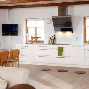 Białe meble kuchenne pięknie prezentują się w towarzystwie beżowej podłogi, drewnianego stołu i wyeksponowanych belek stropowych. Drewnianą podłogę ozdabiają szare, dekoracyjne chodniczki. Fot. Ballingslov, linia Solid.