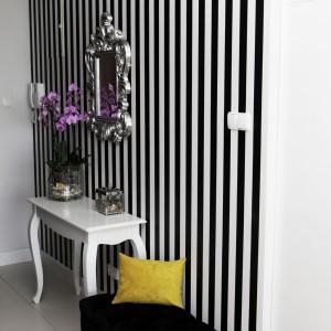 W przedpokoju jedną ze ścian pokryto efektowną czarno-białą tapetę w pionowe pasy, które optycznie powiększają wysokość wnętrza. Powierzchnię udekorowano lustrem w zdobionej ramie, z którym harmonizują stylizowaną komodą i ławeczką, które utrzymano w kontrastujących ze sobą bieli i czerni. Projekt: Chalupko Design. Fot. Chalupko Design.