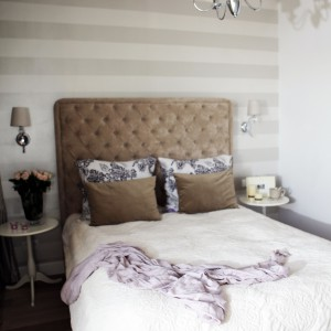 Stylowa i przytulna sypialnia zwraca uwagę tapicerowanym zagłówkiem za łóżkiem, komponującym się kolorystycznie z dekoracyjnymi poduszkami i barwnie dopasowanymi poziomymi pasami na ścianie. Całość utrzymano w delikatnych, ciepłych kolorach. Projekt: Chalupko Design. Fot. Chalupko Design.