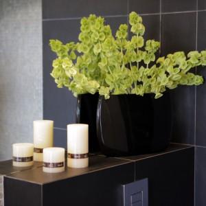 Mieszkanie wykończono z dbałością o każdy detal. Ściany i podłogę w łazience wykończono gresem imitującym kamień. W zestawieniu ze szklaną mozaiką i dużym, prostym lustrem bez ramy, stanowią estetyczne i eleganckie wykończenie. Projekt: Chalupko Design. Fot. Chalupko Design.