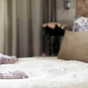 Przytulne i wzorzyste tkaniny nadają wnętrzu elegancki, kobiecy charakter. Jasne kolory wyciszają i zachęcają do relaksu. Projekt: Chalupko Design. Fot. Chalupko Design.